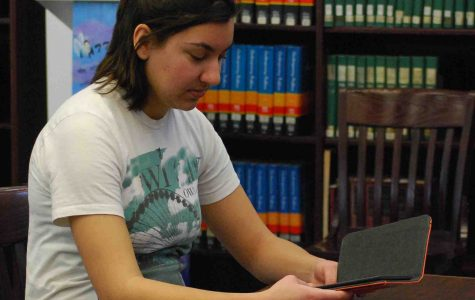 A student reads a book from one of the ten Amazon Kindles in the RHS library. -photo by Nursena Acar