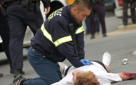 EMT worker Alex Sha attempts to perform CPR on the injuried pedestrian during the EFM's fake car accident.