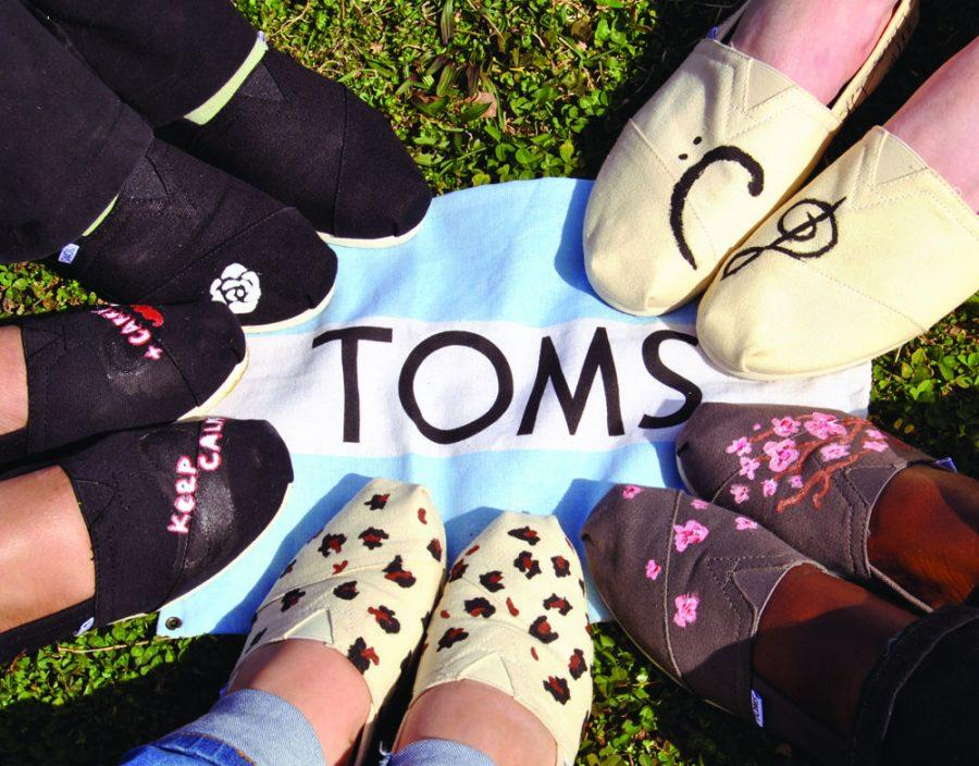 Students+show+off+their+newly-decorated+TOMS+shoes.+TOMS+donates+a+pair+of+shoes+for+every+pair+sold.+Seniors+John+Wambach+and+Jessica+Smith+led+the+shoe+sale+and+Style+Your+Own+Sole+event.+--+Photo+by+Anne+Wagner