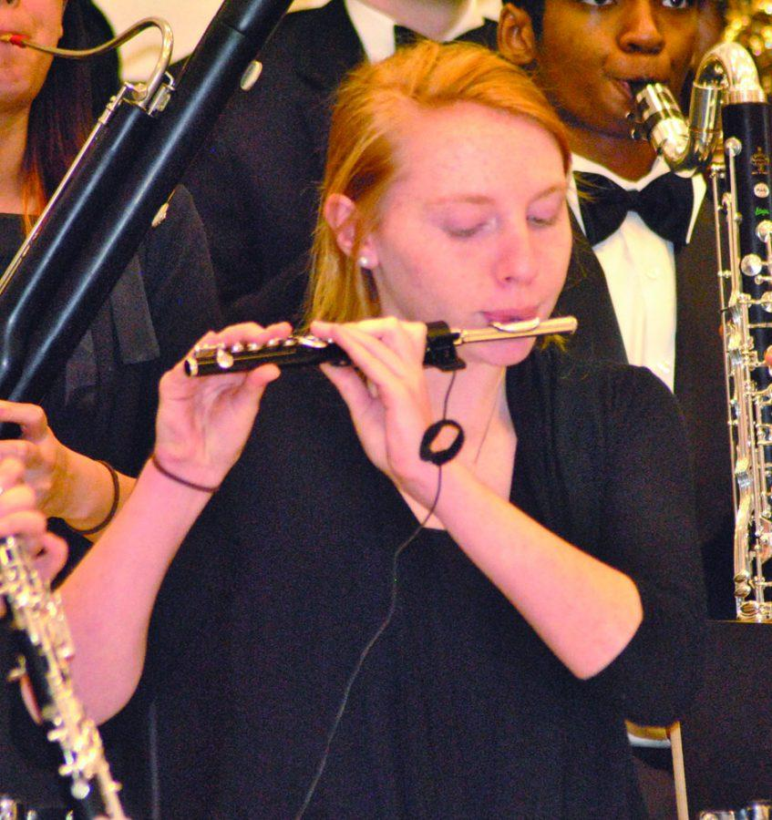 Sophomore+Jennifer+Holler+plays+the+piccolo+in+the+warm+up+room+before+the+band%E2%80%99s+performance.+Holler+is+the+only+piccolo+player+for+the+Symphonic+Band+at+RHS.+