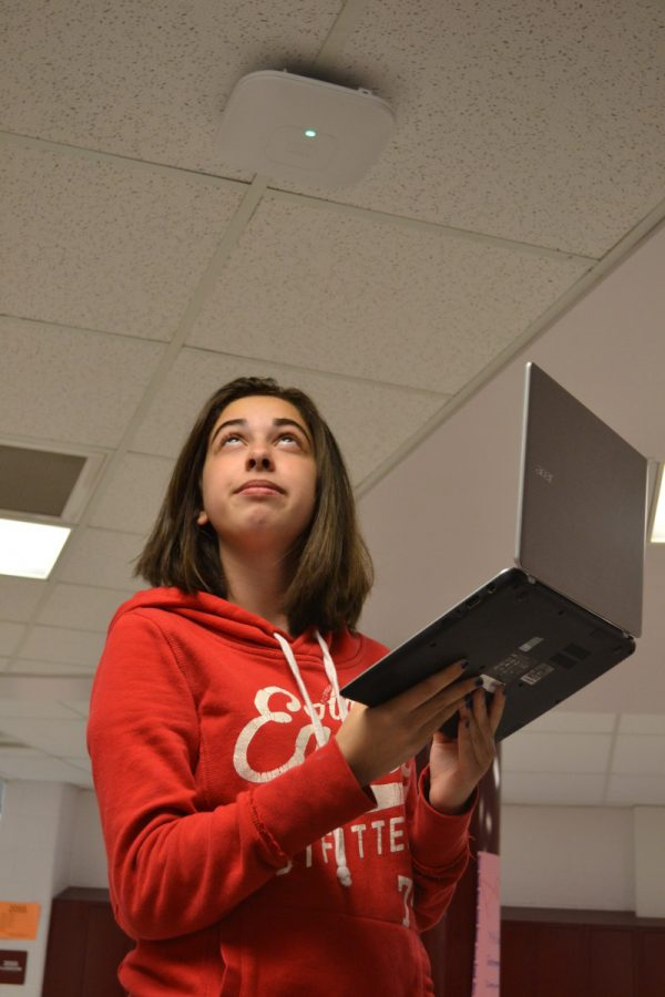 Junior+Michaela+Berger+observes+the+white+Wi-Fi+router+on+a+hallway+ceiling.+Berger+of+ten+brings+her+laptop+to+school.+--Elissa+Britt