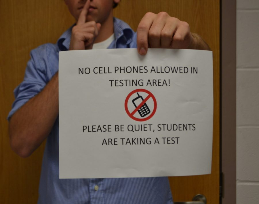A+student+poses+with+a+sign+prohibiting+technology+in+a+testing+room.