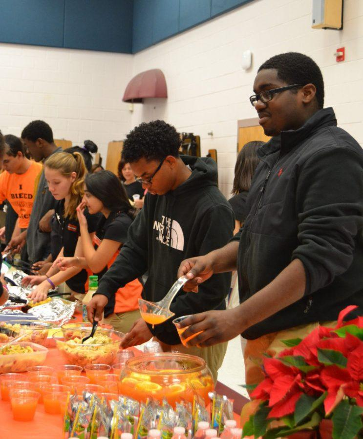 As+attendees+of+the+even+being+to+line+up+for+the+array+of+cultural+food%2C+sophomore+Manny+Essien+serves+up+a+mixed+orange+punch.+