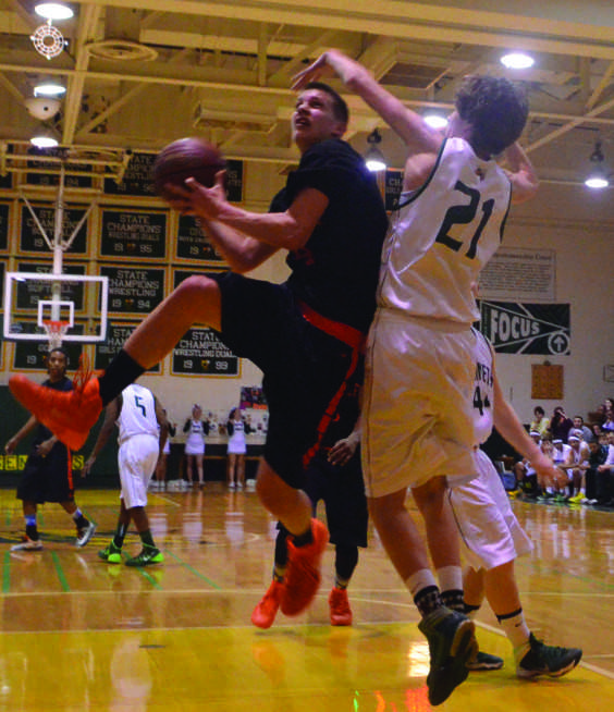 Senior+guard+Brian+Ball+drives+to+the+basket+against+a+Damascus+defender+Feb+20.+Ball%2C+a+captain+of+the+team%2C+had+11+points+and+six+rebounds.+--Adam+Bensimhon
