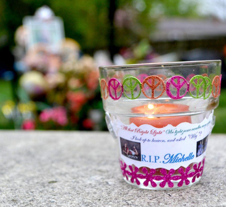 A+memorial+candle+is+placed+near+the+gravesite+of+former+senior+Michelle+Miller%2C+who+was+killed+in+a+murder-suicide+last+April.+Miller%E2%80%99s+friends+and+classmates+came+together+to+remember+her+April+8.+--Camila+Torres