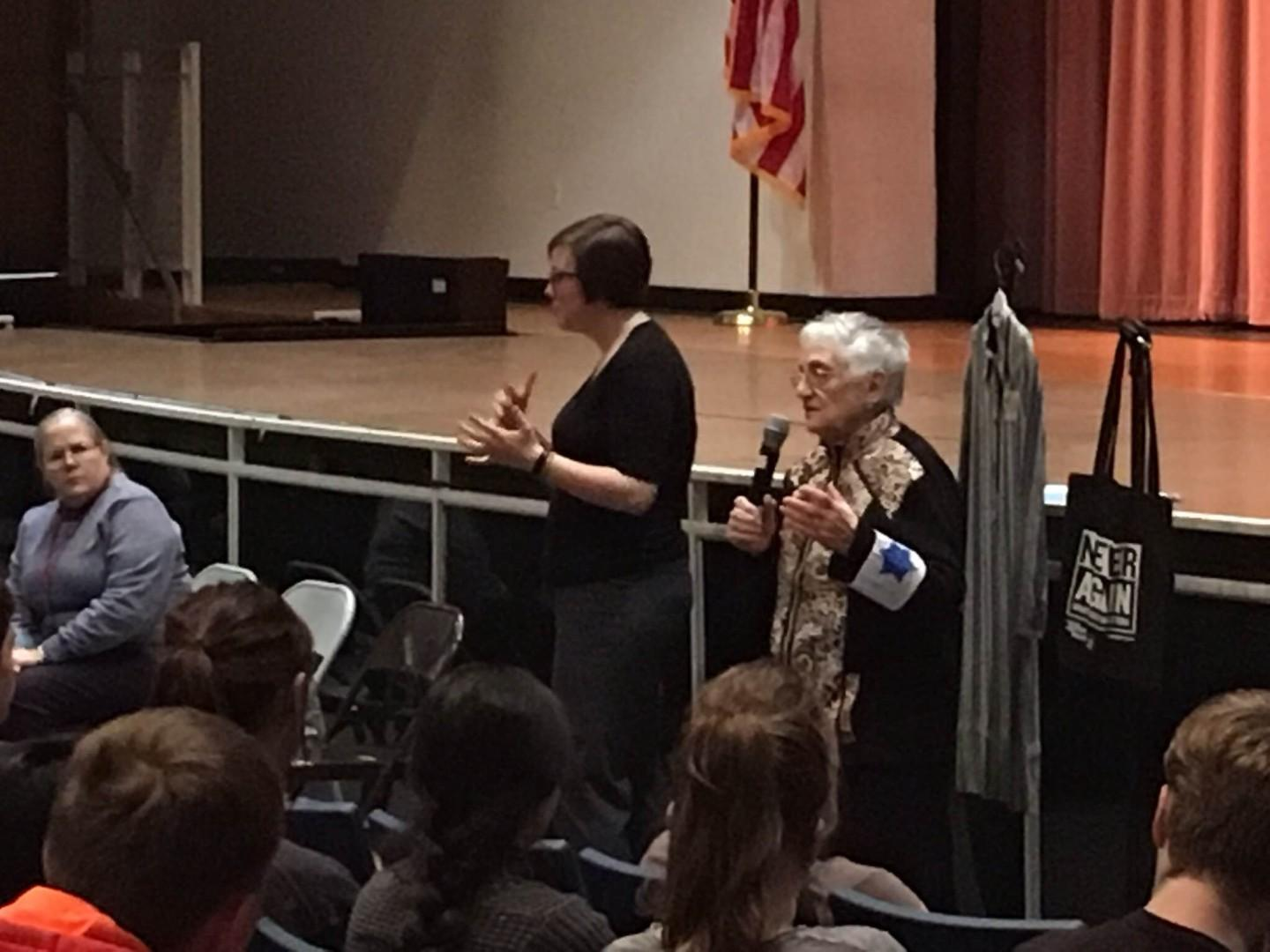 Holocaust survivor Edith Lowy (right) speaks to RHS students Feb. 23. She is wearing a replica of the Star of David armband she was forced to  wear in the Wieliczka ghetto. To her right are a replica of a concentration camp prisoner's outfit and a tote bag from the United States Holocaust Memorial Museum that reads