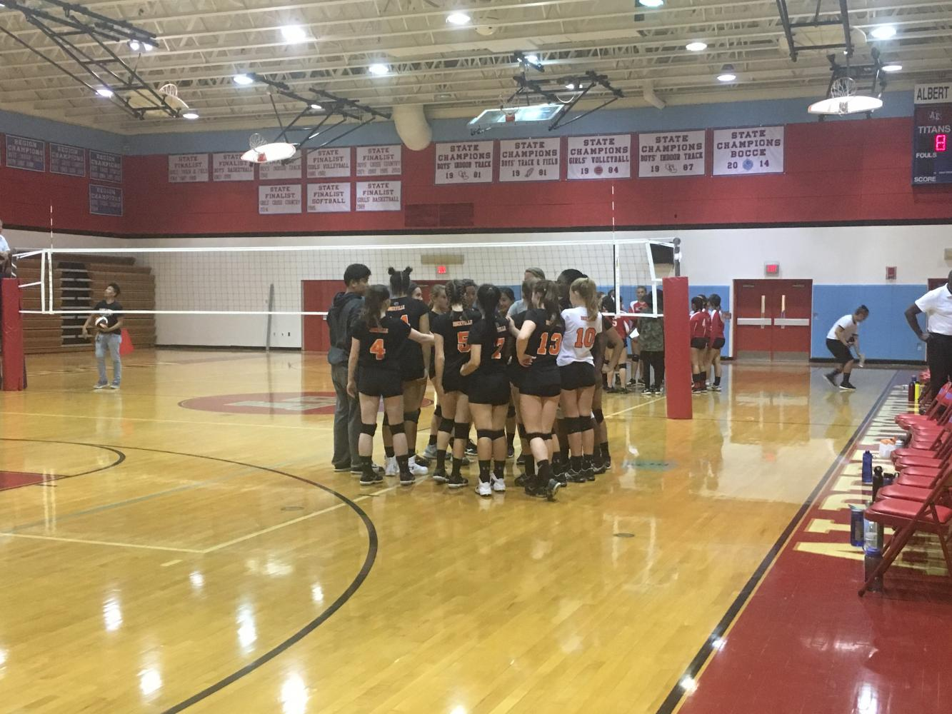 Rams huddle during a timeout against  the Albert Einstein Titans whom they beat in straight sets for their first win of the season.