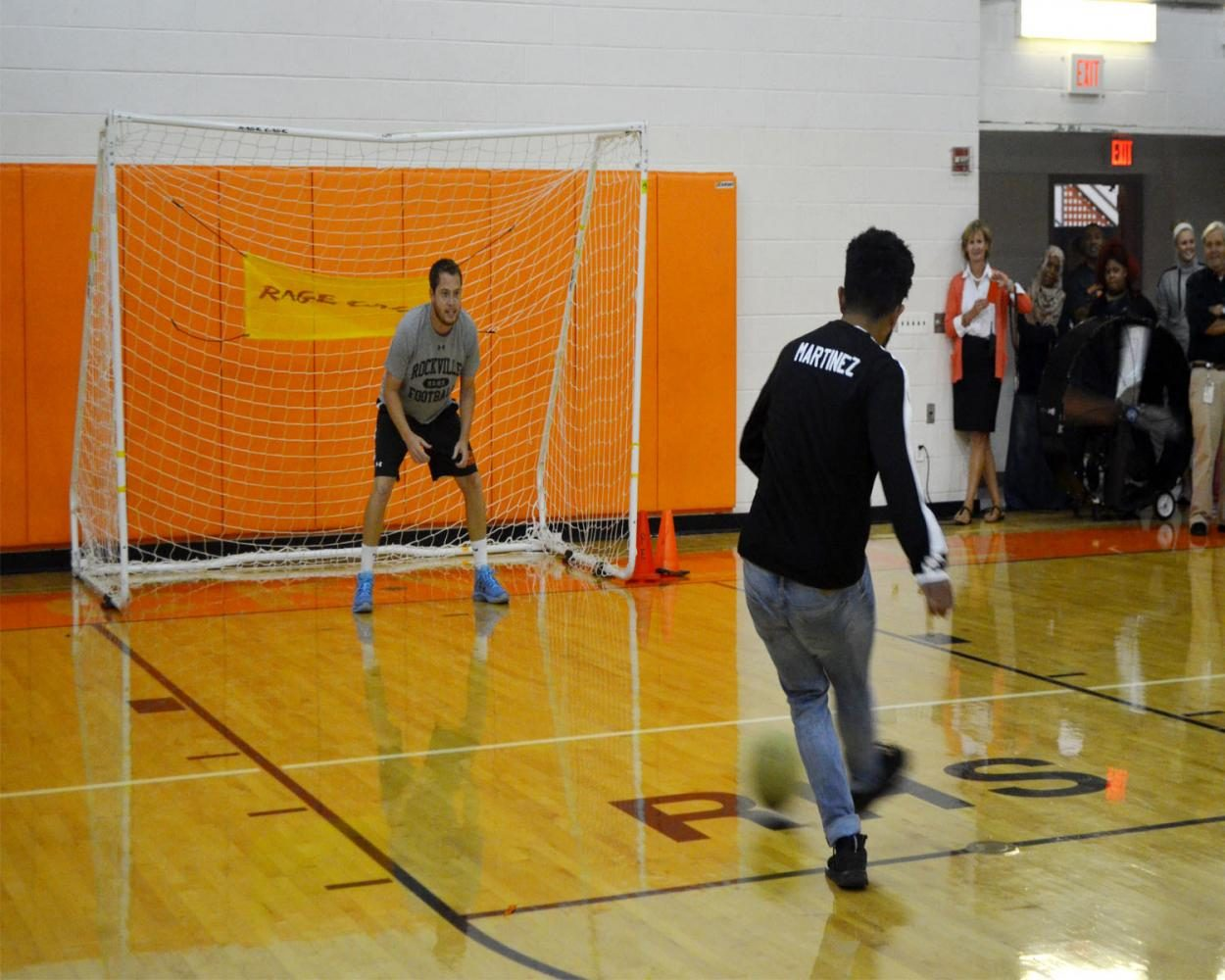 Boys soccer player Ronald Martinez takes a shot at faculty member Jesse Rutter during the final rounds of the boys v girls soccer match up.