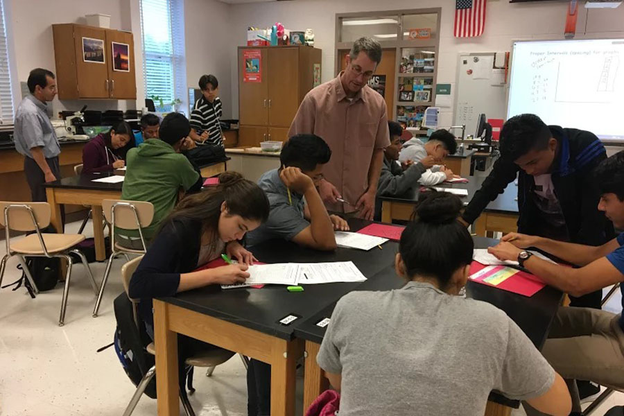 Biology teacher Jeff Grandin works with ESOL students in the new ESOL Biology class.