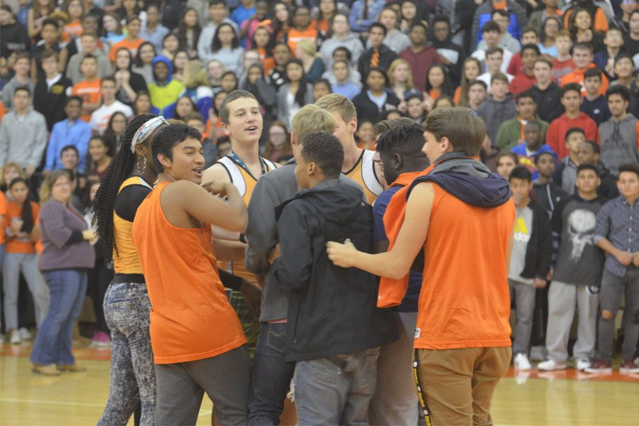 Indoor Track team huddles at half court after being announced.
