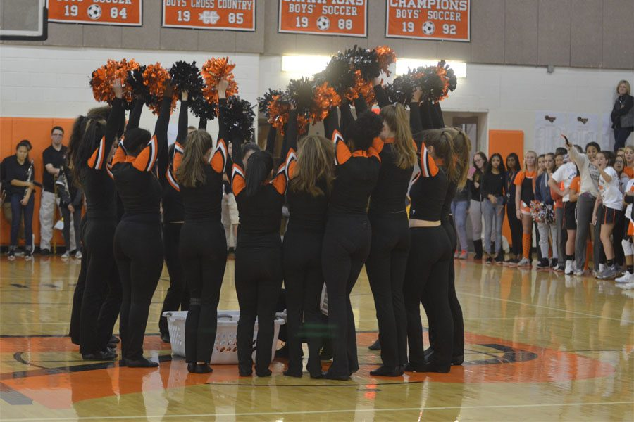 Poms converge in the center of the gymnasium, holding their pom-poms.