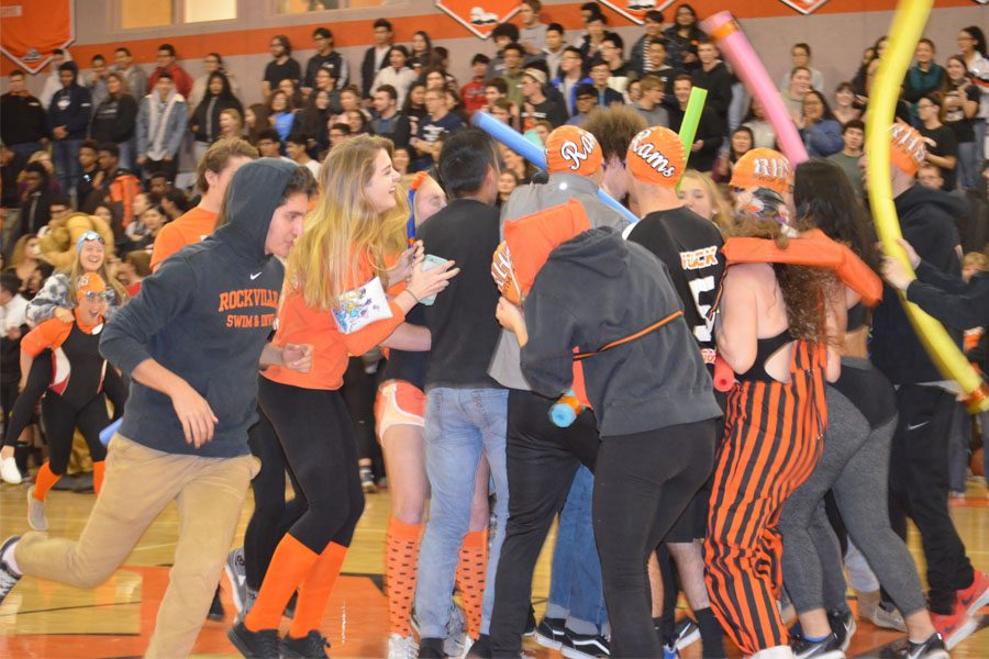 The Swim and Dive team wears swim caps, goggles, and floaties as they run out to half court.