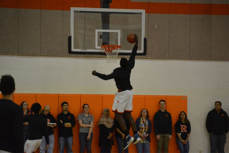 Freshman Jimmy Sorunke throws down a one handed dunk in the winter pep rally.