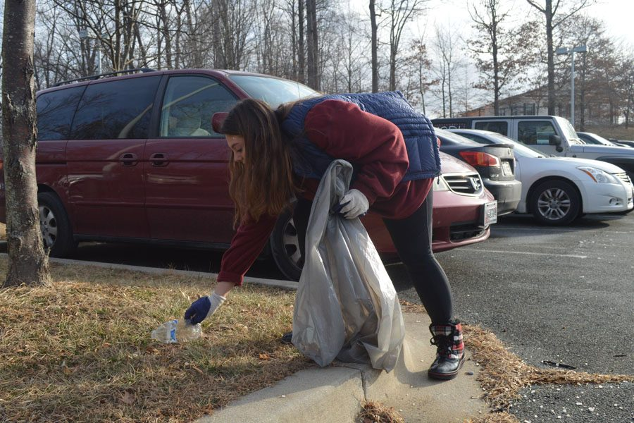 Senior Shoshana Wahl picks up trash in the student parking lot.