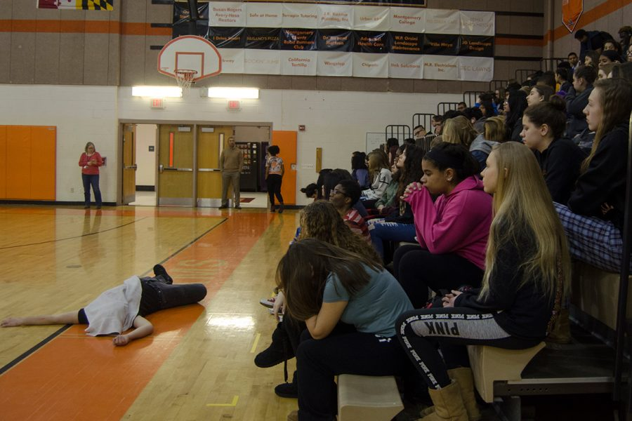 Senior Luke Guthrie plays dead in front of all the students to symbolize the victims of the shooting.