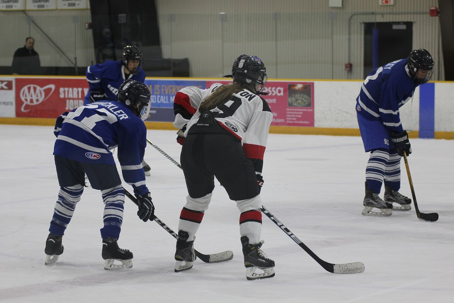 Sophomore Evelyn Leighton (center) skates against the Sherwood Warriors Nov. 7.  She joined varsity this year after playing for JV as a freshman.