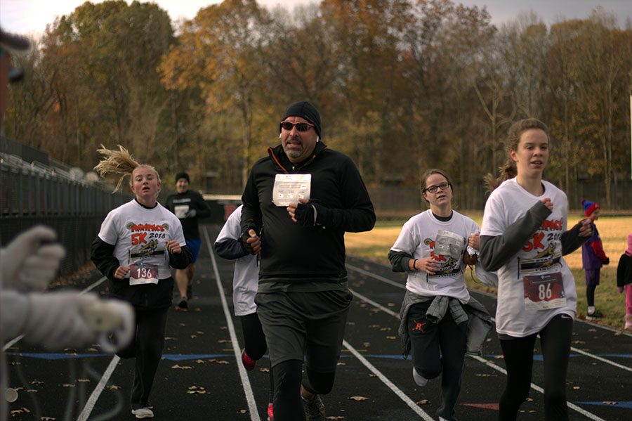 """Students and parents crossing the finish line shared their thoughts with the Rampace.  """"I felt accomplished after finishing the race. I got to run with a bunch of my friends and support the journalism program, which was so worth it,"""" junior Kate Holland (far left) said."""