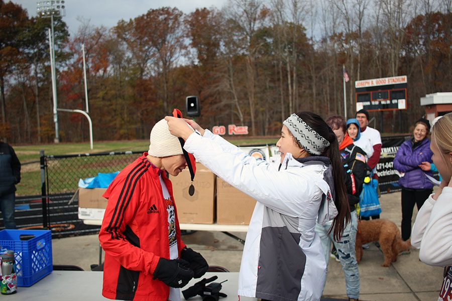 Rampace Editor-in-Chief Elena Mach awards Margaret Campbell a medal for coming first out of all the women runners.