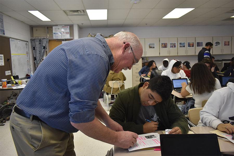 English resource teacher Martin McCarrick, born in County Sligo, Ireland, helps senior Luis Cerna annotate text for his English 12 class.