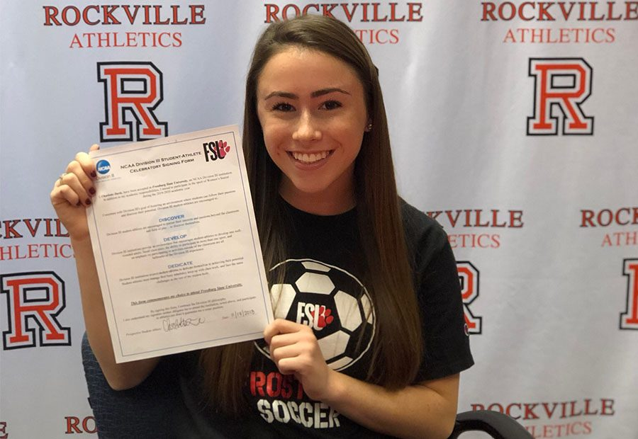 Senior+Charlotte+Davis+holds+up+her+Letter+of+Intent+after+she+signed+to+play+soccer+at+Frostburg+State+University+Nov.+14.