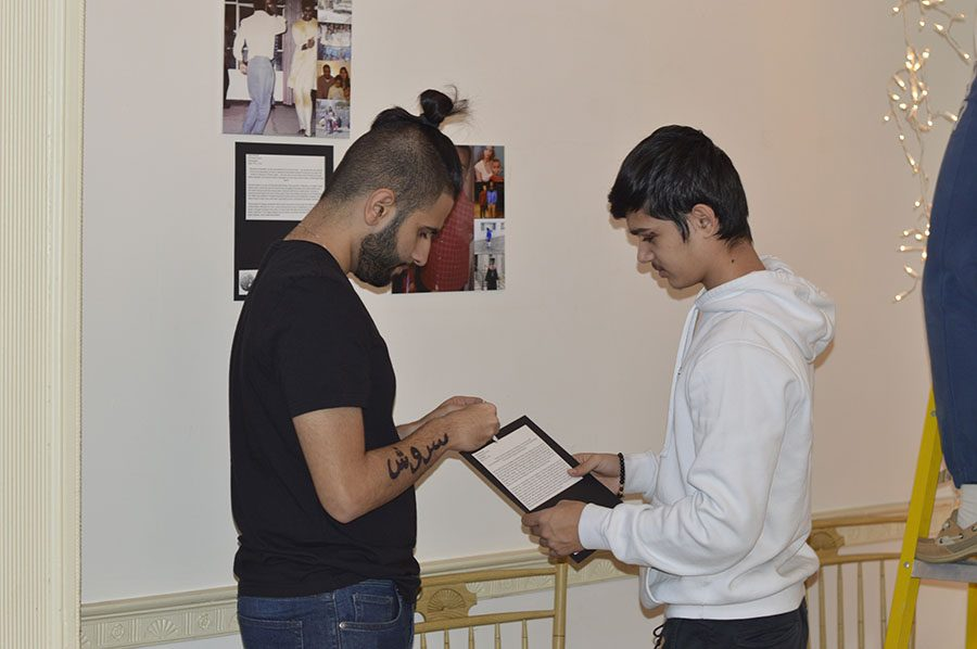 Junior Soroush Noktehdan, left, and junior Kushal Devkota, right, work together preparing their displays at the Beall-Dawson House. AP Lang students created the immigration displays in class in the second quarter.