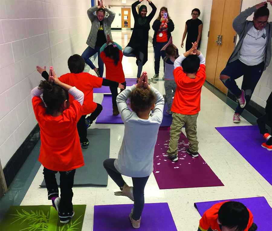 Children perform yoga with RHS students.  The students must plan three activities per week for the children.