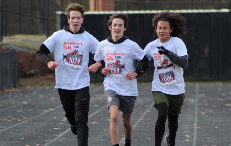 From left to right: cross country teammates senior Michael Carvajal, junior Joe Young and senior Dylan Kim linked arms through the finish line. All three of them have run the Rampace every year of their high school careers.