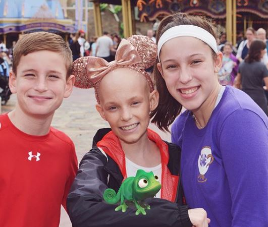 From left to right: Frank Weaver, Lily Weaver and Grace Weaver pose together at Disney World