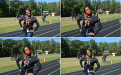 New principal Rhoshanda Pyles poses for a few pictures at the second pep rally of the year. Behind her, teachers set up for musical chairs as part of the homecoming competitions.