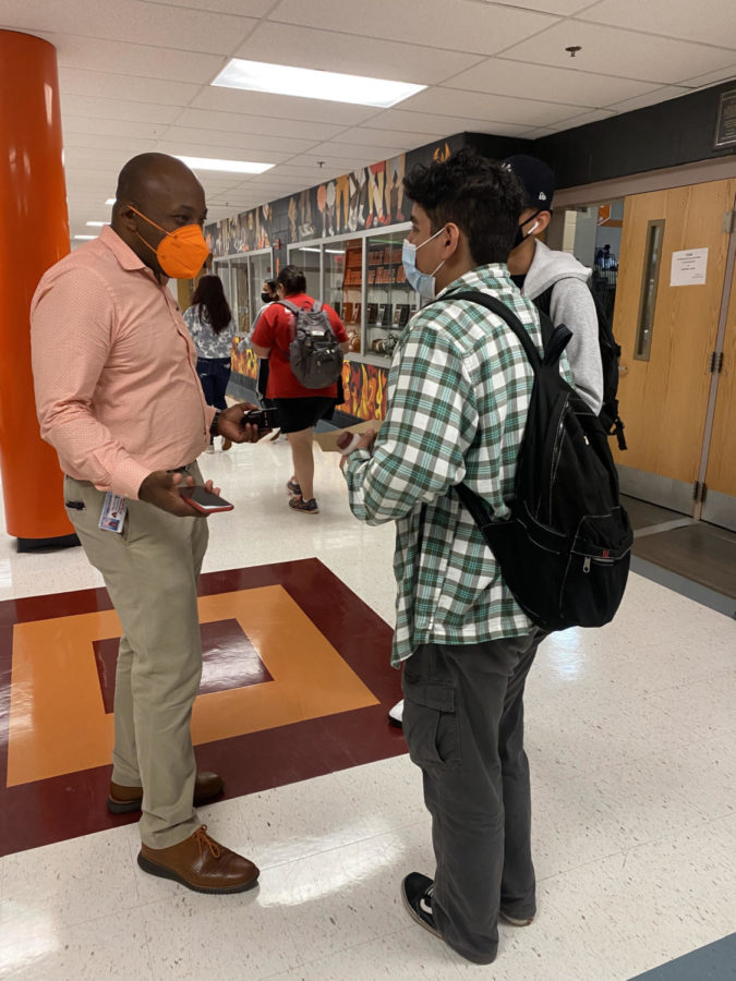 Assistant principal Marcus Wiggins chats with a couple of students about the start of their school year. Wiggins is remembered by many for his positive interactions with students.