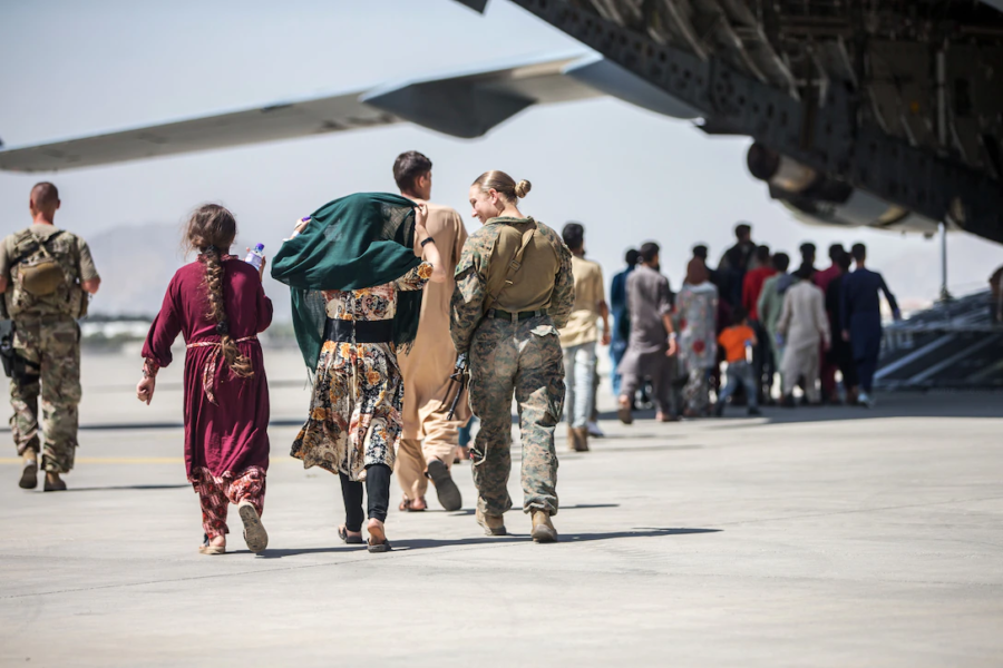 A marine walks with children at the evacuation of Hamid Karzai International Airport in Kabul, Afghanistan, Aug. 24, 2021.